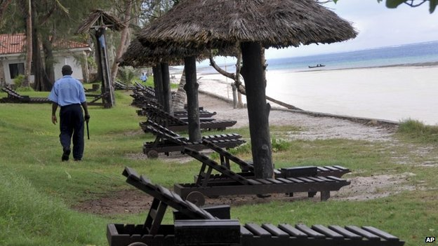 A security guard walks past empty sun loungers facing the Indian Ocean at a holiday resort in the town of Diani, south of Mombasa, on the coast of Kenya Thursday 22 May 2014