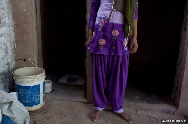 Santraj's daughter stands outside the family's toilet