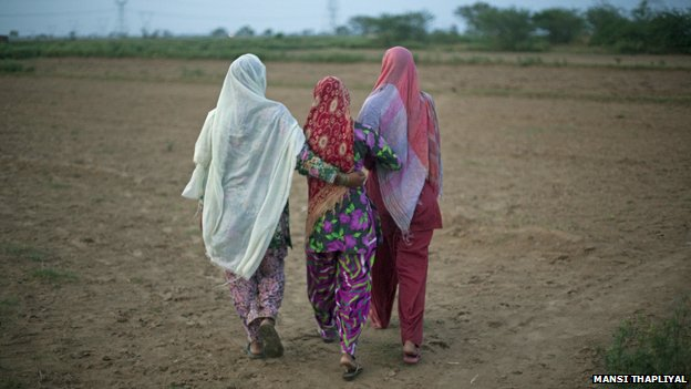 Women walking away from camera in Indian field