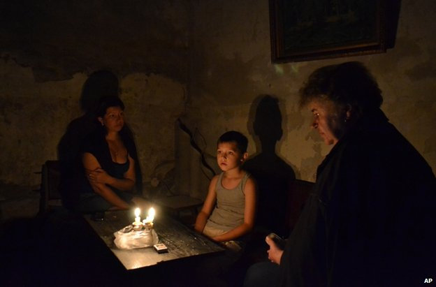 People sit in a bomb shelter in the besieged rebel stronghold of Sloviansk, eastern Ukraine, 22 June
