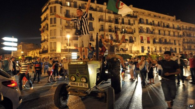An Algerian football fan celebrating on a tractor in Algiers - 26 June 2014