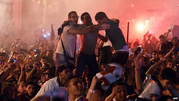 Algerian fans celebrate in Algiers on 26 June 2014 after Algeria eliminated Russia with a 1-1 draw in a Fifa 2014 World Cup Group H match