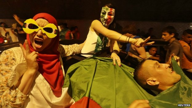 Football fans celebrate with an Algerian national flag after the end of Algeria's 2014 World Cup Group H match against Russia, in Algiers 26 June 2014.