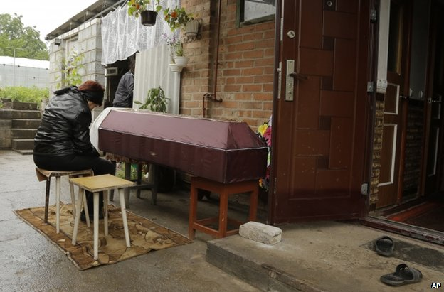 A woman grieves by the coffin of her daughter, 46, said to have been killed in a Ukrainian mortar attack on Sloviansk, 24 June