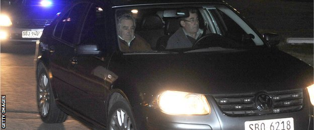 Uruguay's President Jose Mujica (L) leaves in a private car at the Carrasco international airport