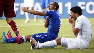 Giorgio Chiellini and Luis Suarez sitting on football pitch