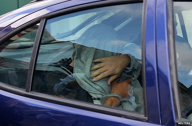 The masseuse of the prominent Pastor family, hidden under a jacket, leaves a police station in a police car during a transfer from Nice to the courthouse in Marseille June 27