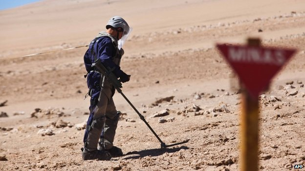 A Chilean army engineers wearing protective gear uses a magnetic detector in a minefield on 26 May 2014