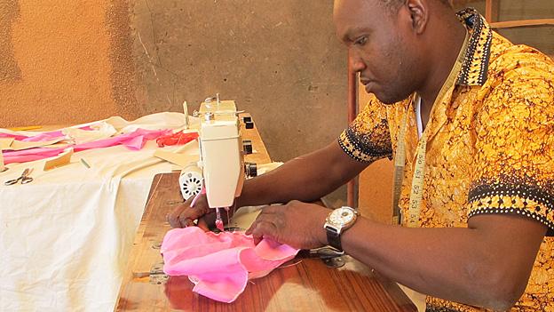 Tailor Oscar Dao working on his treadle machine, Burkina Faso