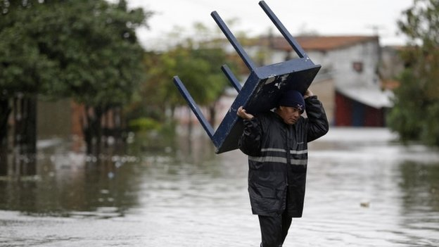 A man carries a table through a flooded street in Asuncion