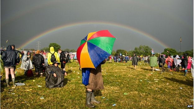 A person holding an umbrella, with a double rainbow visible overhead