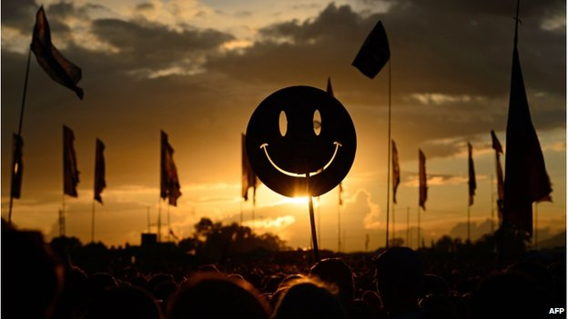 A smiley face sign in silhouette at sunset at Glastonbury
