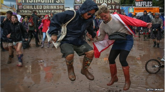 Two people wearing wellies jump in a puddle