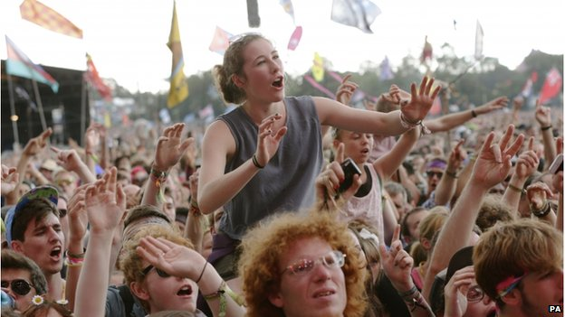 A woman on someone's shoulders in the crowd at Glastonbury