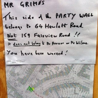 Notice fixed to wooden panels around the Banksy artwork