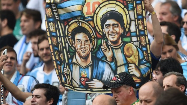 An Argentina fan holds an image of Argentina forward Lionel Messi and former footballer Diego Maradona as saints