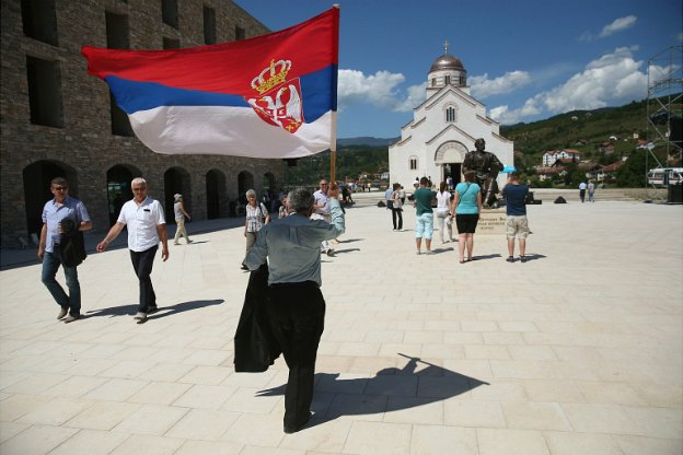 A man waves a Serbian flag as he walks through the mock-village of Andricgrad in Visegrad, Bosnia and Herzegovina - 28 June 2014