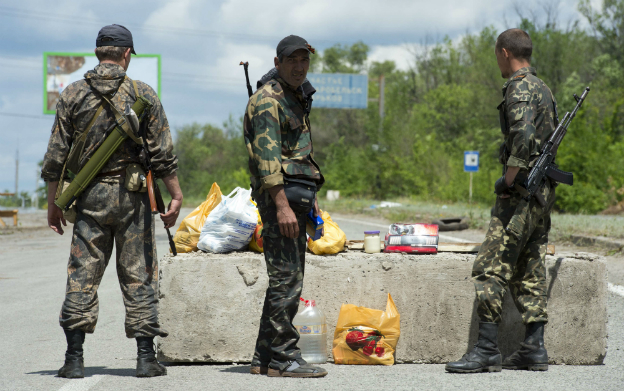 Armed pro-Russians stand guard at a checkpoint outside the town of Metalist, north of Luhansk - 28 June 2014