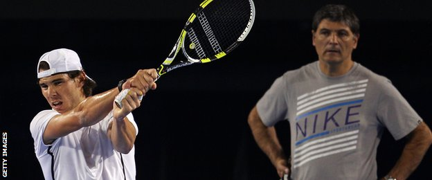 Rafael Nadal of Spain plays a backhand as he is watched by Toni Nadal, his uncle and coach.