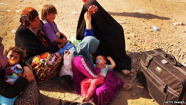 Iraqi families wait outside of a displacement camp for those caught-up in the fighting in and around the city of Mosul 28  June 2014