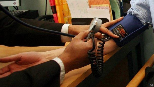 GP checking blood pressure