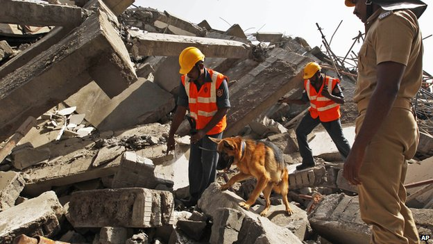 Rescuers with a sniffer dog search for workers believed buried in the rubble of a building that collapsed late Saturday during monsoon rains on the outskirts of Chennai, India, Sunday, June 29