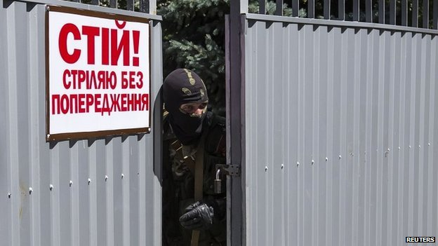 "A pro-Russian gunman next to a sign that reads ""Stop! shoot without warning"" at a captured Ukrainian National Guard compound in Donetsk city - 28 June 2014"