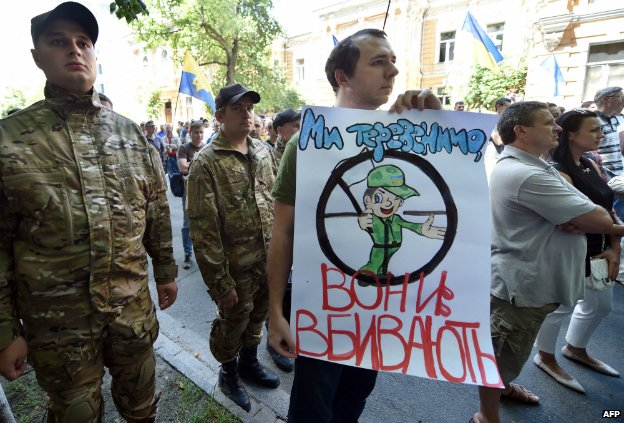 """A man holds a sign saying """"We talk - they kill!"""" during a protest against the ceasefire in Independence Square in Kiev - 29 June 2014"""