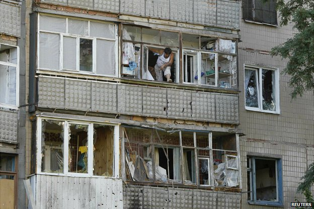 A local resident peers out through a damaged window in an apartment block in Sloviansk that was reportedly shelled - 29 June 2014