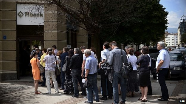 People queue in front of a branch of Bulgaria's First Investment Bank in Sofia on June 27, 2014