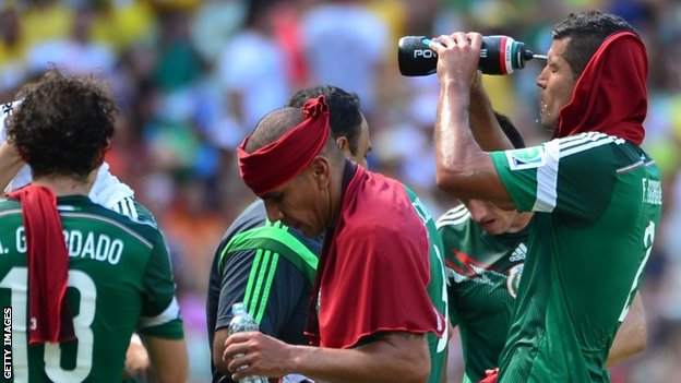 Mexico defender Francisco Rodriguez (right) waters his face
