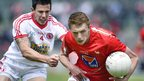 Tyrone defender Conor McAliskey closes in on Louth's John Bingham in the All-Ireland SFC round one qualifier at Healy Park