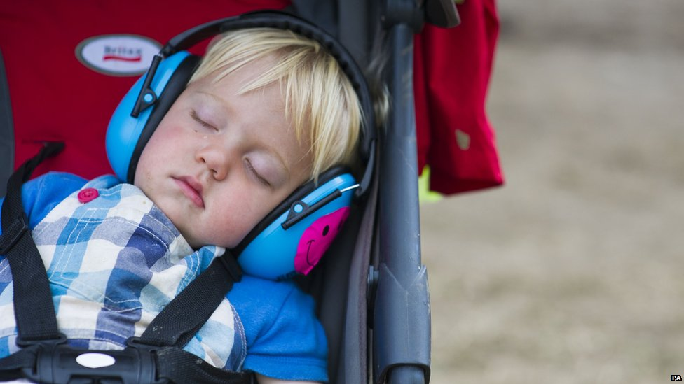 A toddler sleeps at Glastonbury festival