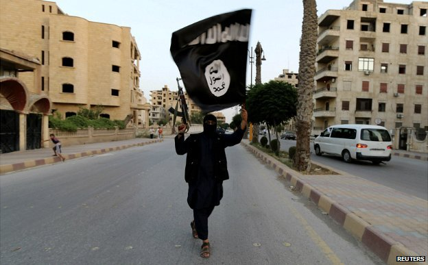A gunman in the Iraqi city of Raqqa waves an Isis flag - 29 June 2014