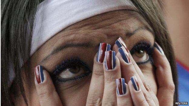 A woman reacts as she watches a screening of 2014 World Cup round of 16 match between Costa Rica and Greece on TV in San Jose on 29 June, 2014.