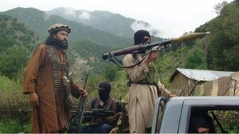 In this file photo taken on Sunday, Aug. 5, 2012, Pakistani Taliban  patrol in their stronghold of Shawal in Pakistani tribal region of South Waziristan