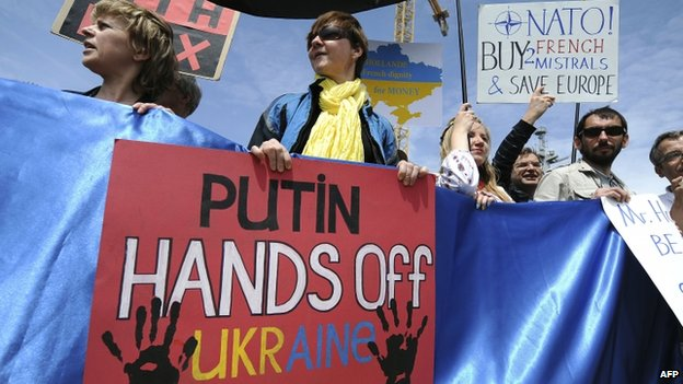 Protesters hold Ukrainian flags and placards during a demonstration in front of the French built Vladivostok warship being sold to Russia in Saint-Nazaire, western France (1 June 2014)