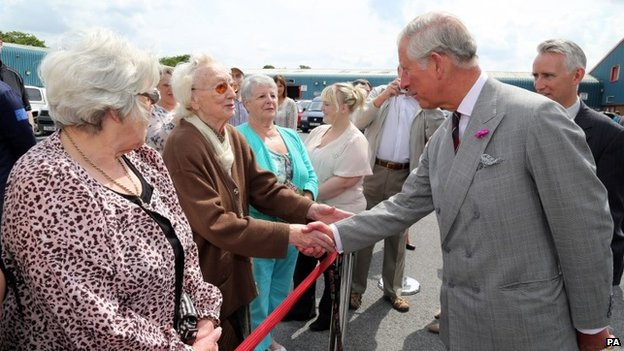 Prince Charles is greeted by 95-year-old Nancy Davies of Llandybie outside the Cnwd factory