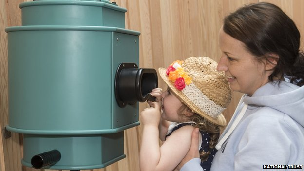 Child and woman looking at optical instrument at Porth y Swnt