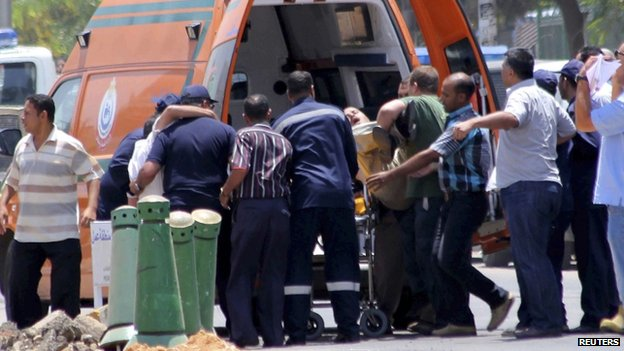 People injured in bomb blasts are transported to an ambulance in Cairo (30 June 2014)