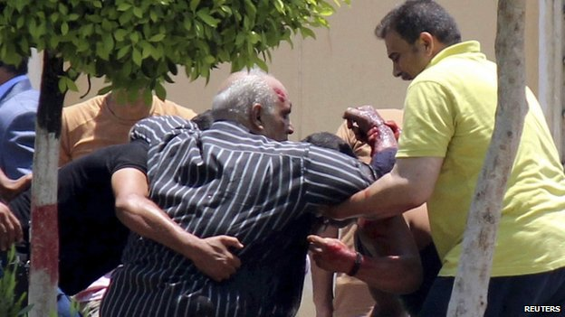 People help a man injured in the bomb blast in Cairo (30 June 2014)