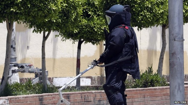An explosive investigator carries a bomb detector as the police search for possible bombs in front of the presidential palace in Cairo (30 June 2014)