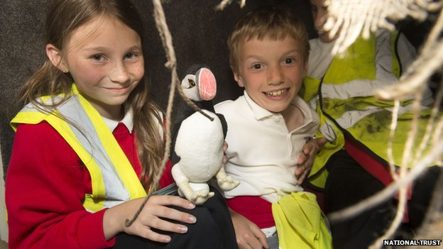 School children hold a puffin toy at the opening of Port y Swnt