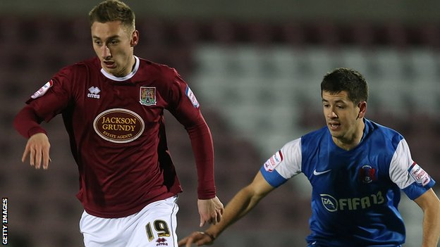 Louis Moult carries the ball while being followed by  Lloyd James of Leyton Orient