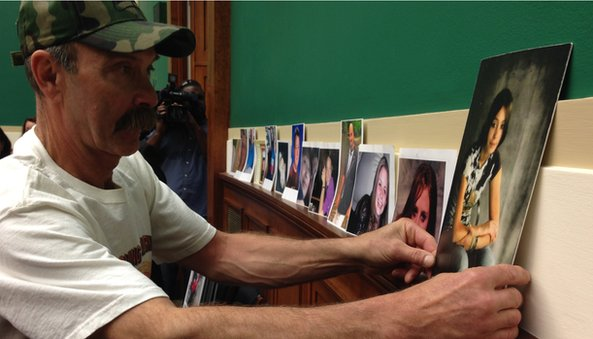 Randall Rademaker placing picture of daughter Amy on wall in Congressional hearing