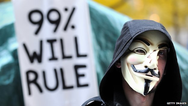 "An Occupy Wall Street protestor holds up a sign that reads, ""99% will rule""."