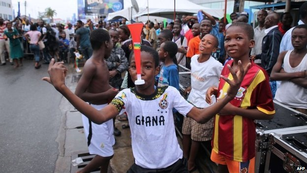 A child poses with a vuvuzela as Ghana supporters react while watching the  World Cup 2014 football match between Ghana and Portugal on 26 June  2014 in Accra.