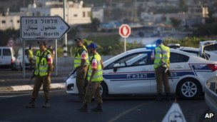 Israeli police officers block a road with their police vehicles in the village of Halhul, near the West Bank