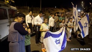 Israelis pray and hold flags at the entrance to Halhul north of Hebron, West Bank
