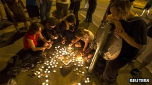 People lighting candles in memory of the three dead teenagers